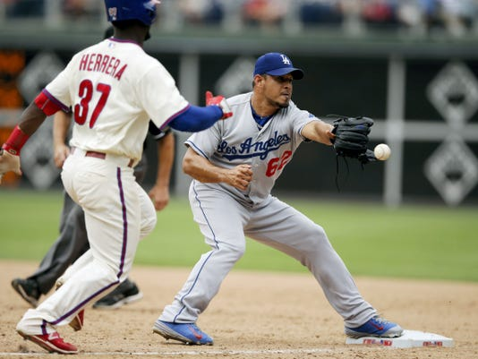 Los Angeles Dodgers' relief pitcher Joel Peralta, right, cannot handle the throw to first base on a single by Philadelphia Phillies' Odubel Herrera during the ninth inning Thursday in Philadelphia.