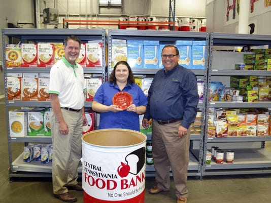 Brad Peterson, from left, director of communications and marketing, Central Pennsylvania Food Bank; Jackie Dahms, manager of Royer's Flowers & Gifts in West York, which collected the most pounds of any Royer's store; and Greg Royer, Royer's president and CEO of Royer's, pose with food collected during Royer's Stems Hunger.