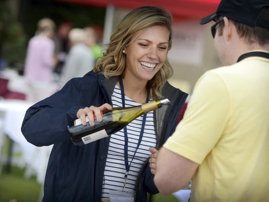 Miranda Sergas of Southern Wine & Spirits, King of Prussia, serves tastings from the Robert Mondavi wine collection. The grounds at Hershey Hotel became the venue for tasting more than 80 different wines, selections from different breweries, and culinary samplings from award winning chefs during the Hershey Wine and Food Festival.