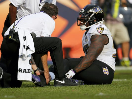 Baltimore's Terrell Suggs is treated on the field during the second half of Sunday's game. Suggs tore his left Achilles tendon, an injury that will end his season.