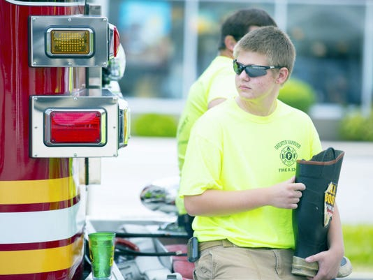 Josh Otis of the Greater Hanover Professional Firefighters rests on the bumper of a Penn Township fire engine while raising money for Fill The Boot on Aug. 8 at the Grandview Plaza.