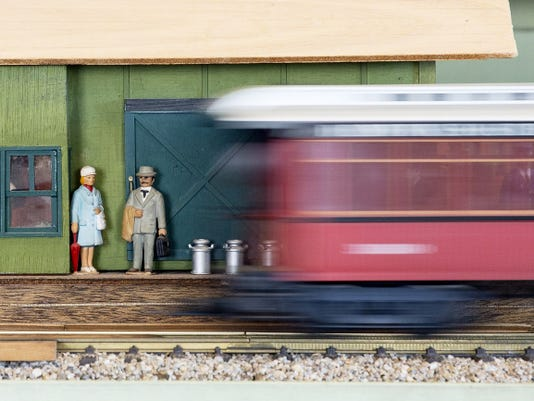 A model train speeds in front of two figurines waiting in a model train station during the Community All Aboard Day at the New Oxford train station Saturday.