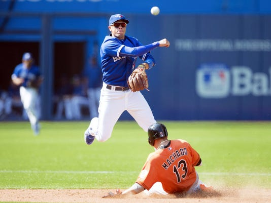 Toronto Blue Jays' Ryan Goins, left, turns a double play over Baltimore Orioles' Manny Machado during the eighth inning of Saturday's game in Toronto. The Blue Jays won, 5-1.