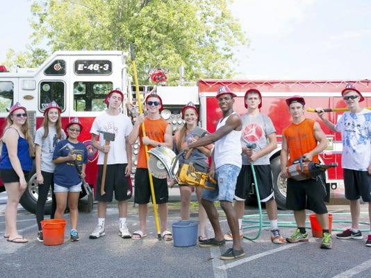 Hanover High School seniors stand in front of the Hanover Fire Department engine they had just cleaned, posing for a group picture with firefighting tools that were aboard the fire engine.