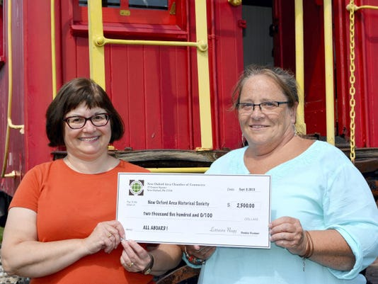 New Oxford Area Chamber of Commerce President Lorraine Nagy, left, presents a check to Anita Kennedy-Muccino, chairperson of the All Aboard! Committee. The New Oxford Area Historical society has been raising funds to purchase the property to ensure that the 102-year-old station is around for future generations.