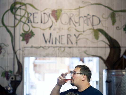 James Chorba of Drums sips wine at Reid's Orchard & Winery on a recent Saturday.