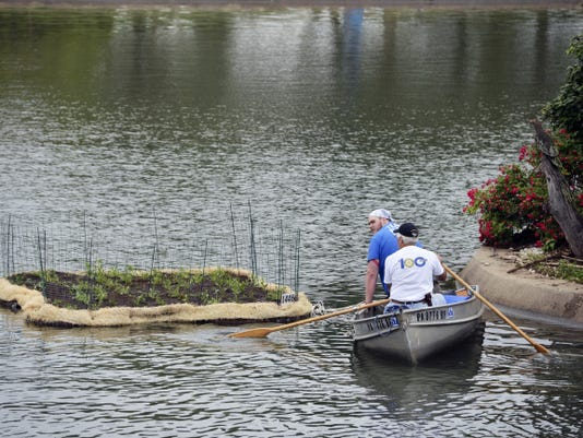 The Rotary Club of York's Preserve Planet Earth Committee installs a floating island at Kiwanis Lake in June. The island, with native wetland plants, is designed to filter excess nutrients and pollutants from the water. This is just one of the local environmental projects that York Rotary leads.