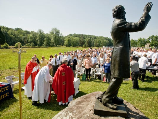 Members of the clergy take Holy Communion during Mass led by The Rev. John Jenkins, president of the University of Notre Dame, near the statue of Civil War chaplain William Corby at Gettysburg National Military Park on Saturday, June 22, 2013 in Gettysburg, Pa. The event was hosted by the Notre Dame Club of Gettysburg, with mostly alumni and school officials in attendance.