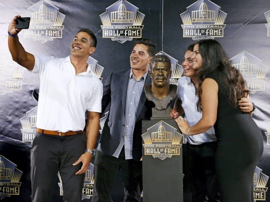 Children of former NFL player Junior Seau, from left: Jake, Tyler, Hunter and Sydney. The group posed for a selfie with the bust of their late father during inductions at the Pro Football Hall of Fame on Saturday in Canton, Ohio.