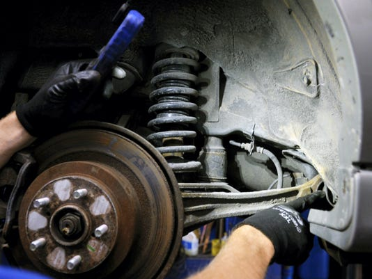 "Service manager Chad Fadely points out an inner tie rod end that needs to be replaced as he demonstrates a safety inspection on a Subaru on June 26. ""The cars today are built to last longer. If you keep 'em maintained, and you take care of the car, the car'll take care of you,"" Fadely said."
