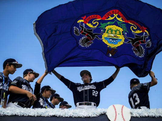 The Little League team from Red Land, including Cole Wagner, center, show off the Pennsylvania flag during the Little League Baseball World Series Grand Slam Parade on Wednesday in South Williamsport. Red Land is the first team from York County to reach the World Series. The Mid-Atlantic Region champions open play at 8 p.m. Friday against the Midwest Region champions from Webb City, Mo.