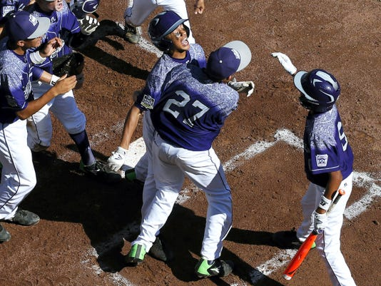 Pearland's Raffi Gross, center, is hugged by teammate Ben Gottfried (27) as he is swarmed after hitting a two-run home run during Sunday's game in the Little League World Series in South Williamsport. The Red Land team takes on Pearland at 8 p.m. Wednesday for a spot in the U.S. championship game.