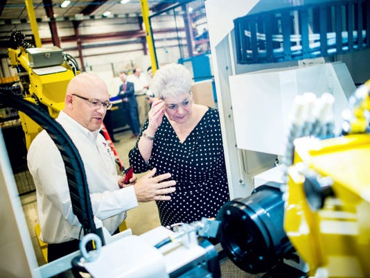 Kathy Manderino, secretary of the Pennsylvania Department of Labor and Industry, right, talks with Weldon Solutions President Travis Gentzler during a press tour of the company in West Manchester Township on Wednesday. Gentzler was describing the machine visible, which uses robotic controlled mechanisms to perform precision grinding of metals.