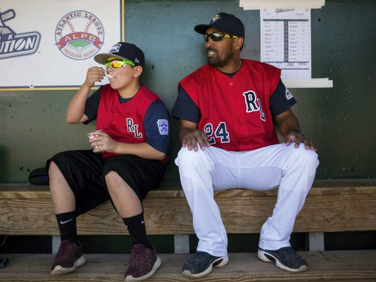 Red Land Little League team member Ethan Phillips eats water ice while hanging out in the dugout Sunday with Revolution bench/third base coach Enohel Polanco before the Revs' game against the Somerset Patriots.