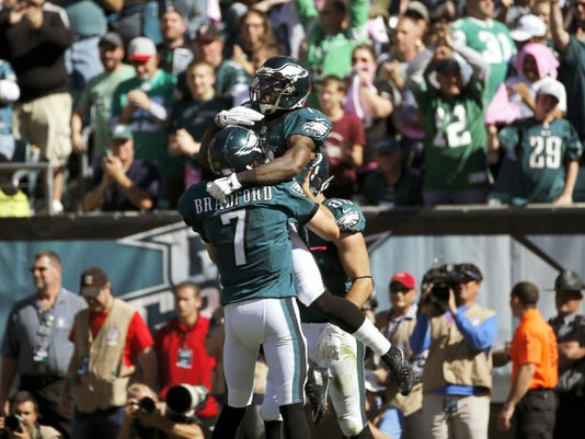 Philadelphia's Sam Bradford, left, and Josh Huff celebrate after Huff's second-quarer touchdown during Sunday's game against New Orleans in Philadelphia. After falling behind in the first quarter, Bradford got the Eagles' offense on board with a 41-yard catch-and-run TD pass to Huff, who did a flip into the end zone to tie the score.