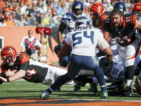 Cincinnati quarterback Andy Dalton (14) scores a touchdown during the second half of Sunday's game against Seattle in Cincinnati. The Bengals won, 27-24, to remain undefeated after Dalton orchestrated a 17-point fourth-quarter rally.