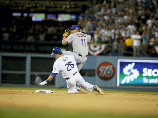 New York Mets' shortstop Ruben Tejada (11) spins behind the Dodgers' Chase Utley, left, who broke up a double play Saturday in Los Angeles.