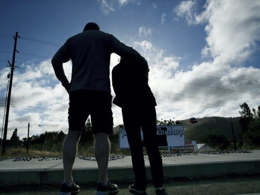 FILE - In this Saturday, Oct. 3, 2015 file photo, Dave Griffiths, left, puts his arm around his wife, Robin Griffiths, as they visit a memorial near the road leading to Umpqua Community College in Roseburg, Ore. Armed with multiple guns, Chris Harper Mercer, walked in a classroom at the community college Thursday and opened fire. (AP Photo/John Locher, File)