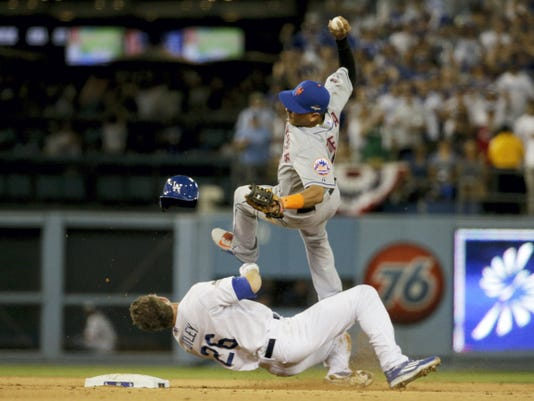 New York Mets shortstop Ruben Tejada, goes over the top of Los Angeles Dodgers' Chase Utley who broke up a double play during the seventh inning in Game 2 of baseball's National League Division Series, Saturday, Oct. 10, 2015 in Los Angeles. (AP Photo/Gregory Bull)