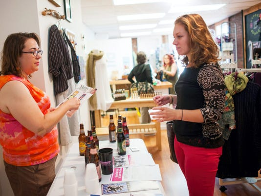 Emily Apat, left, of Beer Ace talks through beer samplers with customer Laura Abbott inside of Sweet Melissa's during an event last year. During June's First Friday, Beer Ace and Brewery Products will offer games on North Beaver Street.