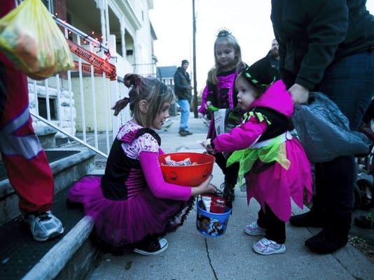 MacKenzie Brooks, of Thomasville, hands out candy to Rosalie Laughman, right, of Hanover for Hanover's trick-or-treat night in 2013.