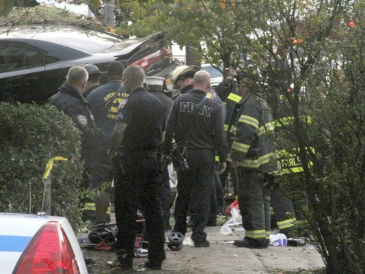 First responders examine an automobile after its driver lost control and plowed into a group of trick-or-treaters Saturday, Oct. 31, 2015 in New York. Three people were killed in the crash, including a 10-year-old girl. Several others were injured. (AP Photo/David Greene)