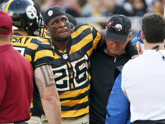 Pittsburgh Steelers running back Le'Veon Bell (26) is helped by a team doctor after injuring his right knee against the Cincinnati Bengals on Sunday in Pittsburgh. Bell was driven off the field, and did not return to the game.
