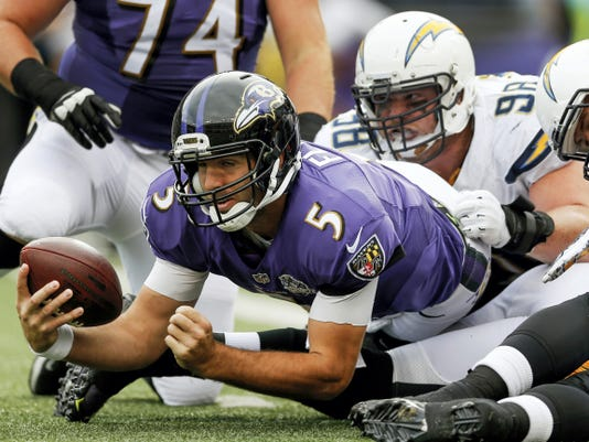Baltimore Ravens quarterback Joe Flacco (5) is hauled to the turf by San Diego Chargers nose tackle Sean Lissemore (98) during the first half on Sunday. Flacco rallied the Ravens to a victory.