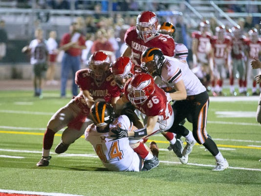 Bermudian Springs players pile on top of Hanover's Hunter Martz during Friday's game at Bermudian Springs High School. The Nighthawks won, 22-14, in the Division III opener for both teams.