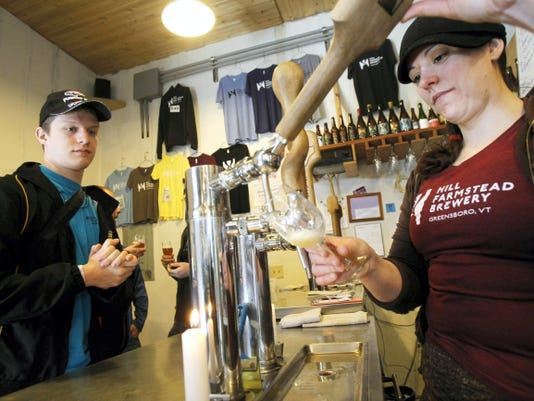 Jordan Aders from Indiana, left, watches as Kerrie Montgomery draws a beer tasting at Hill Farmstead Brewery in Greensboro, Vt. Hill Farmstead beer is not yet shipped out of state.