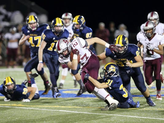 Shippensburg's Cameron Tinner (27) bullies his way down field despite pressure from Greencastle's Kyrin Zimmerman (31) and Brae Peck (83) on Friday night. The Greyhounds won, 23-10.