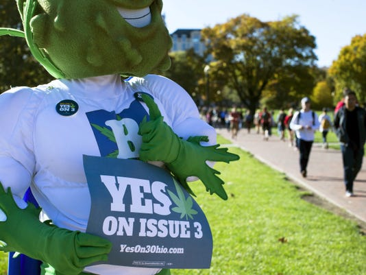 Buddie, the mascot for the pro-marijuana legalization group ResponsibleOhio, holds a sign as he gives a thumbs-up to students at the Ohio State University oval on election day, Tuesday, Nov. 3, 2015, in Columbus, Ohio. Eligible Ohioans rejected a measure that would have allowed marijuana to be grown, processed and consumed within the state's borders. (AP Photo/John Minchillo)