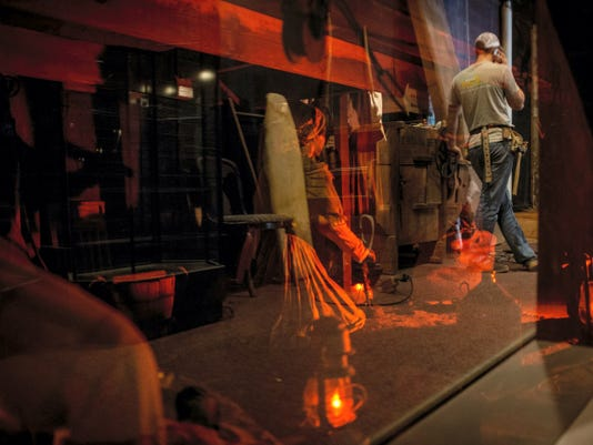 A construction worker stands on break, reflected in a wax rendition of the Underground Railroad at the Gettysburg Heritage Center on Thursday, Feb. 6, 2014. The museum plans to auction off the majority of its old wax figurines, their clothing, props and other exhibit fixtures.