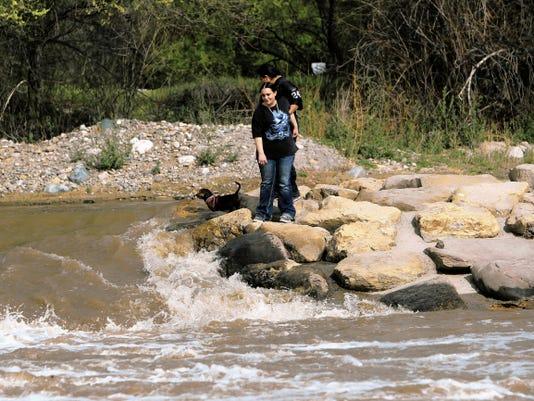People on Wednesday walk along the Animas River at Berg Park in Farmington.