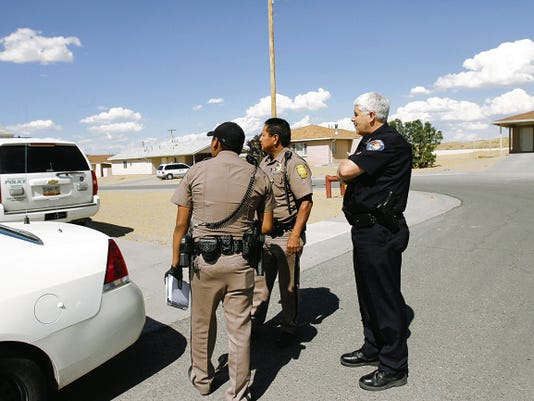Navajo Police Officer Jonathan Johnson, left, speaks with Navajo Police Lt. Phillip Joe and Farmington Police Chief Steve Hebbe on Thursday during an investigation at a housing area in Ojo Amarillo.