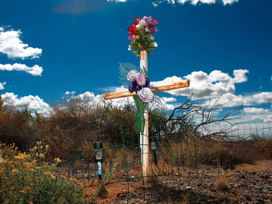 A decorated cross as seen on Tuesday near mile marker 130 south of Bloomfield on U.S. Highway 550 marking the area where a family of four was killed in a crash on the southbound lane.  New Mexico Department of Transportation officials said that routine maintenance on an approximately 120-mile stretch filled in rumble stripping less than a month before the head-on crash.