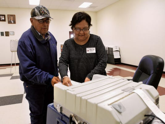 Christine Johnson helps Melvin Caboni cast his ballot last month at the Upper Fruitland Chapter House.