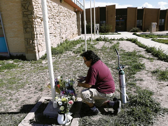 Lorenzo Lee places flowers on March 20 at the base of a flag outside the Navajo Nation Division of Public Safety's Shiprock District Office.