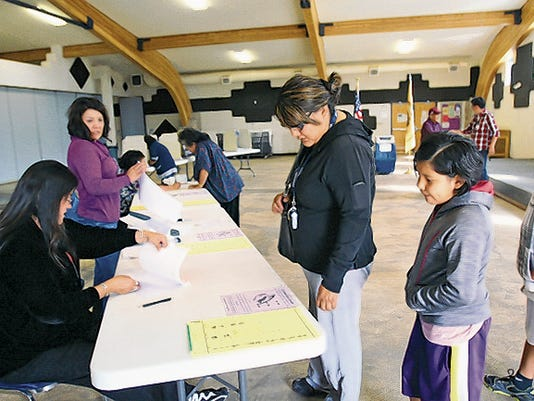 Voters check in on Aug. 26 as they prepare to cast ballots in the Navajo Nation primary election at the Nenahnezad Chapter house in Fruitland.