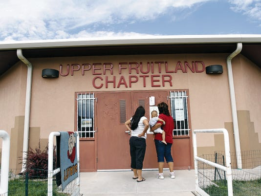 Michelle Baudoin, left, and Jenell Arthur, holding her grandson Tayshawn Nakai, look at a sample ballot for the Navajo Nation primary election on Tuesday before voting at the Upper Fruitland Chapter House in Upper Fruitland.