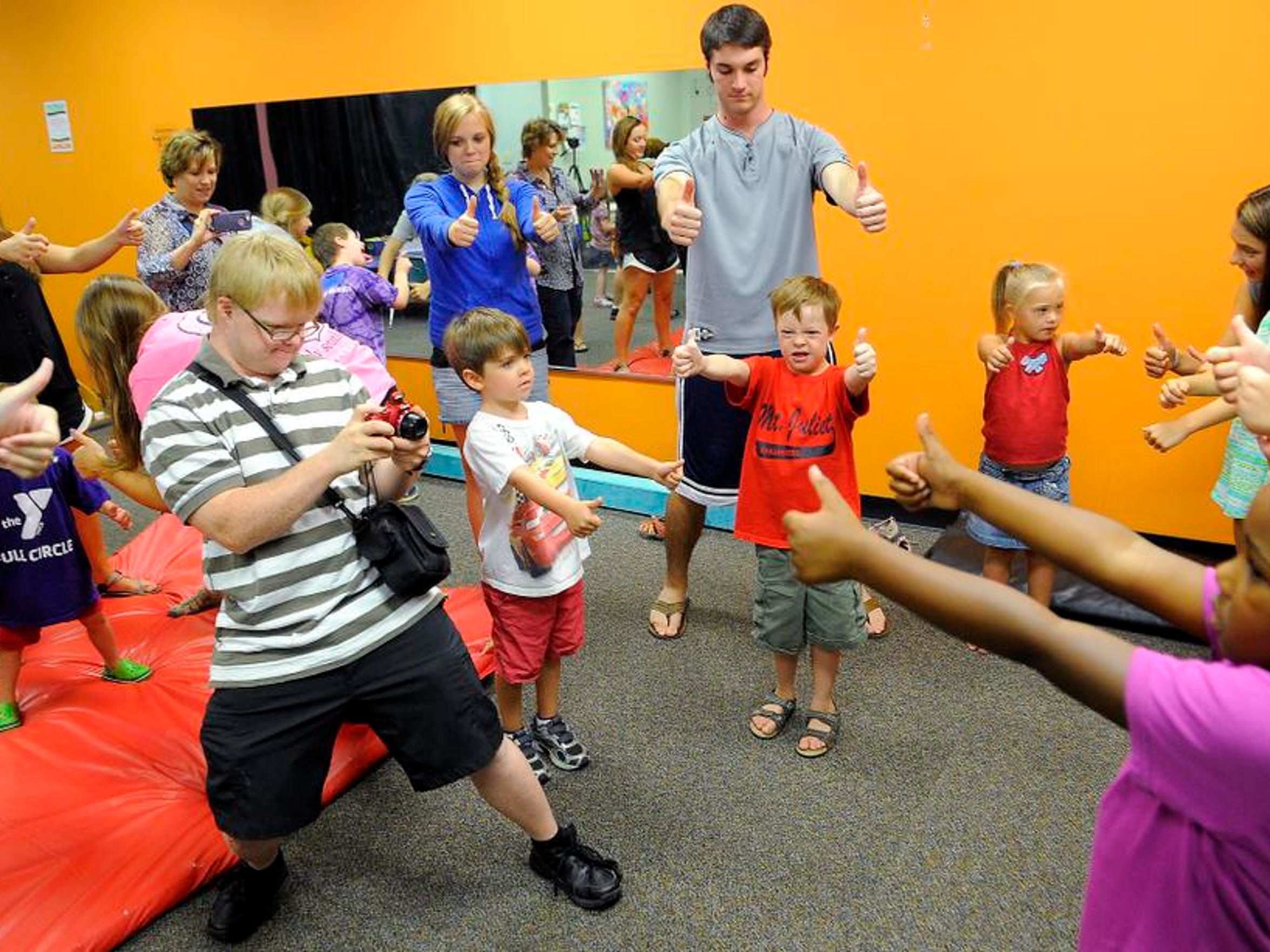 Wanting to be a photographer, Eric Wilson takes photos at DSAMT Friends Camp for Kids on Friday July 25, 2014, in Brentwood, TN.
