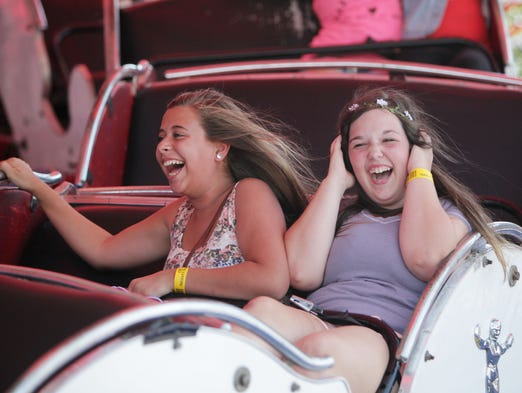 Sydney King, 14, left, and Kenzie Britain, 14, ride the Himalaya at the Ozark Empire Fair on Friday, July 25, 2014.
