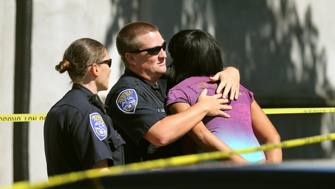 Police try to comfort family and friends as they arrive at the scene where two people were shot, one fatally, in a car on N. Clinton Avenue and Burbank Street on Monday, Sept. 12, 2016.
