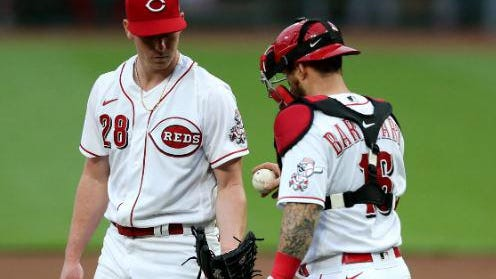 Cincinnati Reds catcher Tucker Barnhart (16) hands the ball to Cincinnati Reds starting pitcher Anthony DeSclafani (28) during a mound visit in the second inning of a baseball game, Monday night, Aug. 31, 2020, at Great American Ball Park in Cincinnati.
