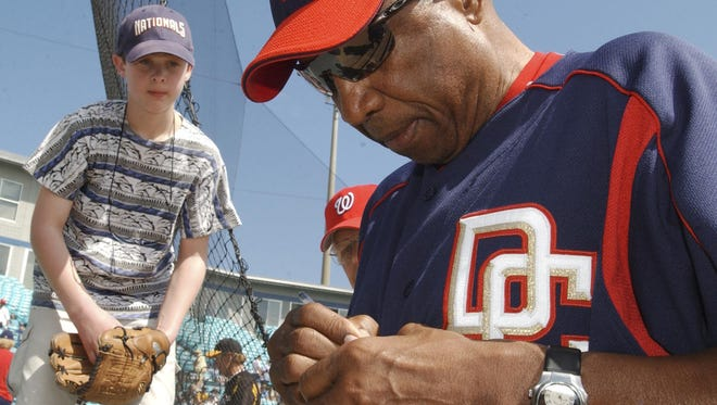 Frank Robinson signs an autograph for a young fan during a spring training game in 2006 at Space Coast Stadium.