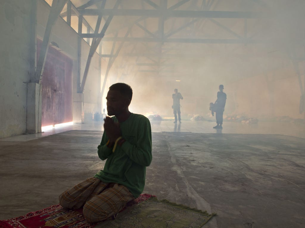 A rescued Bangladeshi migrant  prays at a corner while Indonesian personnel fumigate a warehouse converted into sleeping quarters for migrants at a fishing port in Langsa in Aceh province. The migrants, mostly Rohingyas from Myanmar and Bangladesh, w