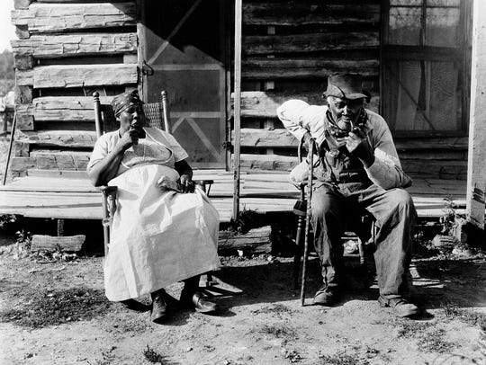 An older couple rest at the end of a workday on a plantation