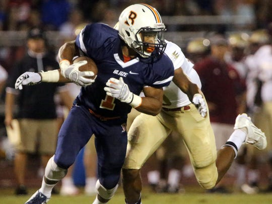 Blackman's Amauri Burks (1) runs the ball as he is tackled by Riverdale's Jarek Campbell (10) at the game at Blackman, on Friday Sept. 4, 2015.