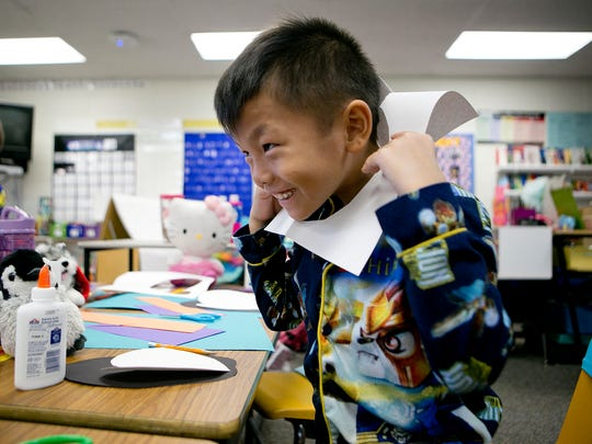 Second-grader Caleb Yang sticks his head through a heart cutout while he was making seasonal decorations with the UWSP softball team at McDill Elementary School in Stevens Point, Friday, Dec. 4, 2015. The UWSP softball team was helping second and third grade students make seasonal decorations to be donated to the assisted living residence at Wellington Place at Whiting.