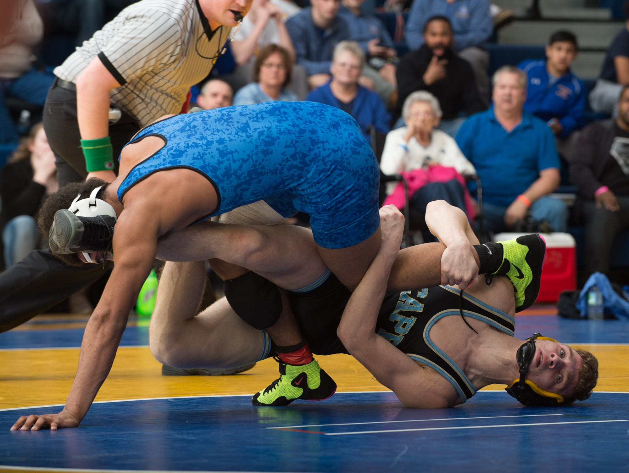 Cape Henlopen's Vincent Diego, right, holds on to the leg of Dover's Anthony Fisher in the 138 pound championship match at the Henlopen Conference wrestling tournament at Sussex Central High School.